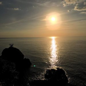 海に沈む夕陽と網掛岩